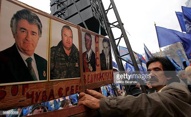 Serbian Radical party supporter holds photos of war crimes suspects Radovan Karadzic Ratko Mladic and Vojislav Seselj at a rally in Belgrade February...