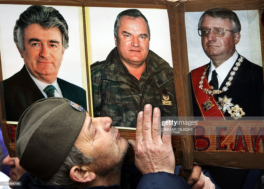 A Serbian Radical party supporter kisses photos of war crimes suspects Radovan Karadzic (L), Ratko Mladic (C) and Vojislav Seselj (R) at the party rally in Belgrade, 24 February 2006. Radovan Karadzic and Radko Mladic are the most wanted war crimes fugitives, while Vojislav Seselj has been detained at the UN tribunal in The Hague for three years, pending trial. A Serbian ultranationalist party on Thursday urged fugitive Bosnian Serb general Ratko Mladic not to surrender to the UN warcrimes court, despite mounting pressure on Belgrade to hand over one of the most wanted suspects of the Balkan wars in 1990s.