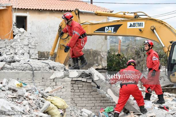 Serbian rescue workers search for survivors through the rubble of a collapsed building on November 27, 2019 in Thumane, northwest of the capital...