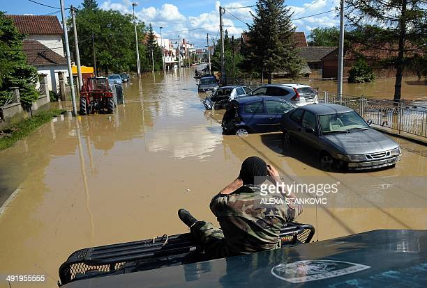 A Serbian rescue workers takes photos of damaged vehicles in the flooded town of Obrenovac 40 kilometers west of Belgrade on May 18 2014 Thousands of...