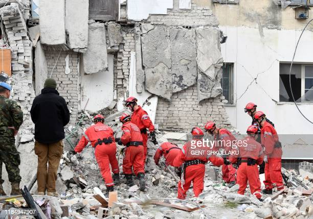 Serbian rescuers look for survivors through the rubble of a collapsed building on November 27, 2019 in Thumane, northwest of the capital Tirana,...