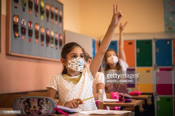 Serbian schoolchildren wearing protective masks to prevent the spread of the novel coronavirus , participate in a lesson on the first day of the new...