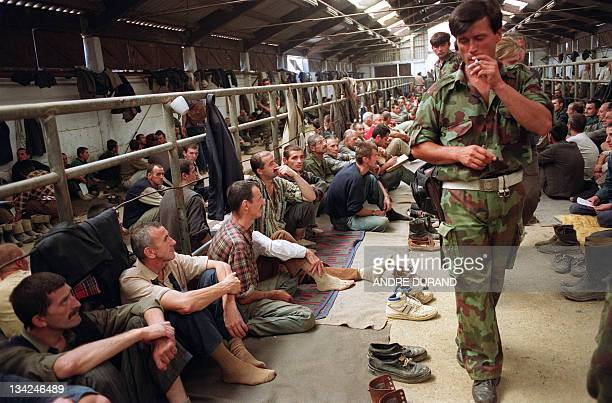 Serbian soldier smoles a cigarette as he guards Bosnian prisoners 14 August 1992 in a farm turned into an internment camp in Manjaca. Some 3.500...