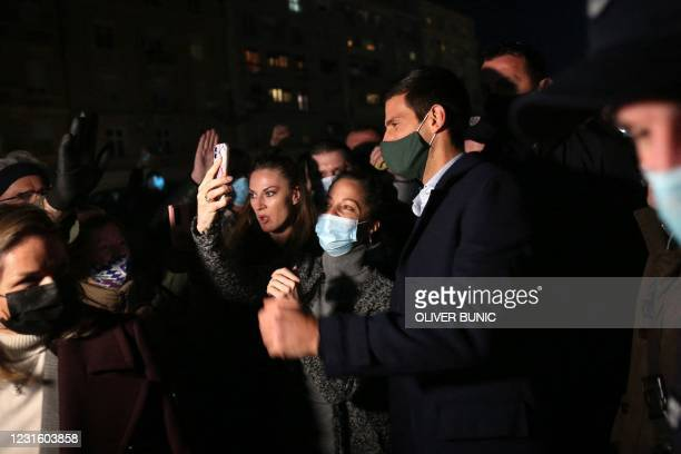 Serbian tennis player Novak Djokovic poses with fans as he watches videos of the most important moments of his career projected onto Belgrade's city...