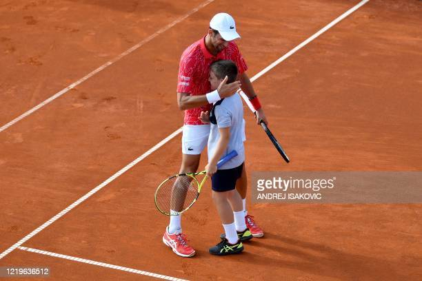 Serbian tennis player Novak Djokovic reacts after exchanigig shots with a ball boy during an exhibition single match at a charity exhibition hosted...