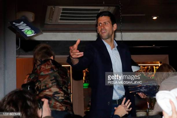 Serbian tennis player Novak Djokovic throws goodies to fans as he celebrates 311 weeks as world number one with his family and supporters in front of...