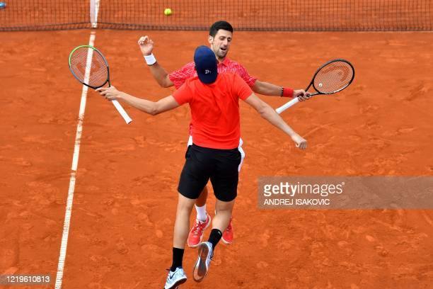 TOPSHOT Serbian tennis players Novak Djokovic and Filip Krajinovic do a chest bump during an exhibition double match at a charity exhibition hosted...