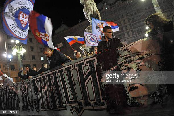 Serbian ultranationalists wave flags of Serbia and hold a banner bearing a picture of former Bosnian Serb army chief Ratko Mladic during a rally to...