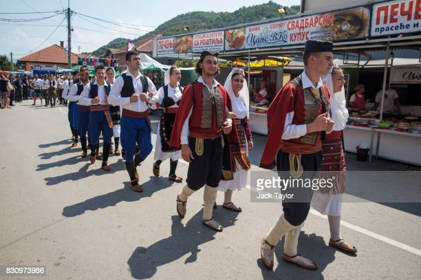 Serbians in traditional dress parade through the town during the Guca Trumpet Festival on August 12 2017 in Guca Serbia Thousands of revellers attend...