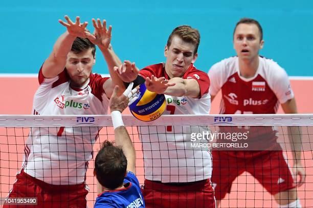 Serbia's Aleksandar Atanasijevic hits the ball as Poland's Piotr Nowakowski and Poland's Artur Szalpuk trie to block during the men's volleyball...