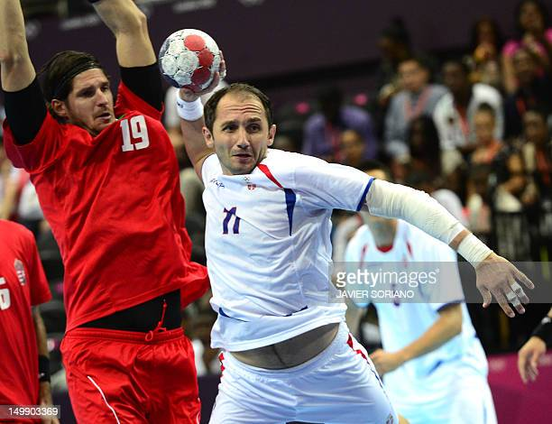 Serbia's Alem Toskic tries to shoot in front of Hungary's rightback Laszlo Zoltan Nagy during their London 2012 Olympic Games men's preliminary Group...