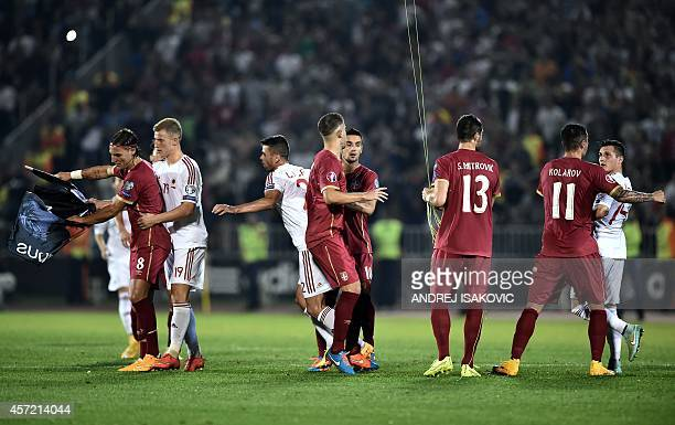 Serbia's and Albania's players scuffle over a flag with Albanian national symbols pulled down by Serbia's defender Stefan Mitrovic from a remotely...