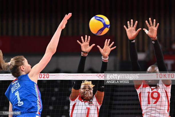 Serbia's Bianka Busa hits the ball in front of Kenya's Jane Wairimu and Edith Mukuvilani in the women's preliminary round pool A volleyball match...