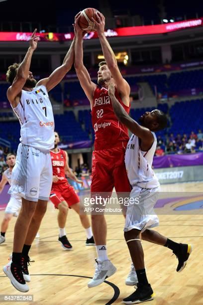 Serbia's center Ognjen Kuzmic goes to the basket between Belgium's forward Axel Hervelle and Belgium's center Kevin Tumba during the men's FIBA...