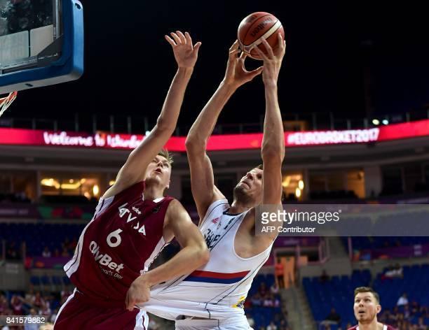 Serbia's center Ognjen Kuzmic vies for the ball with Latvia's power forward Kristaps Porzingis during the FIBA Eurobasket 2017 men's group D...