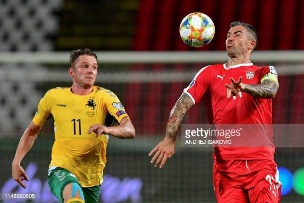 Serbia's defender Aleksandar Kolarov fights for the ball with Lithuania's midfielder Arvydas Novikovas during the Euro 2020 football qualification...