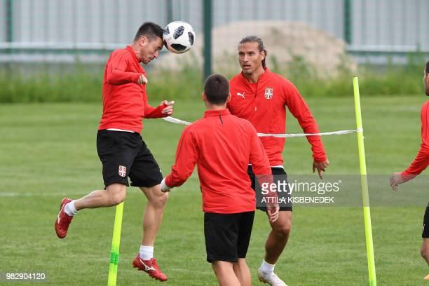 Serbia's defender Antonio Rukavina heads the ball with Serbia's forward Aleksandar Prijovic during a training session at Serbia's base in Svetlogorsk...