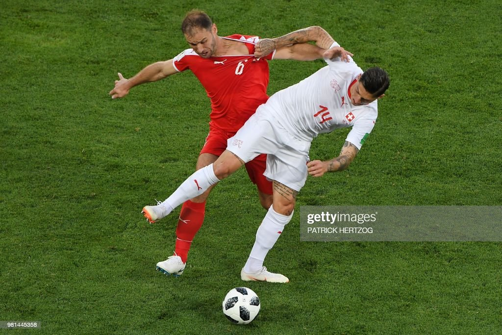 TOPSHOT - Serbia's defender Branislav Ivanovic (L) vies for the ball with Switzerland's midfielder Steven Zuber during the Russia 2018 World Cup Group E football match between Serbia and Switzerland at the Kaliningrad Stadium in Kaliningrad on June 22, 2018. (Photo by Patrick HERTZOG / AFP) / RESTRICTED