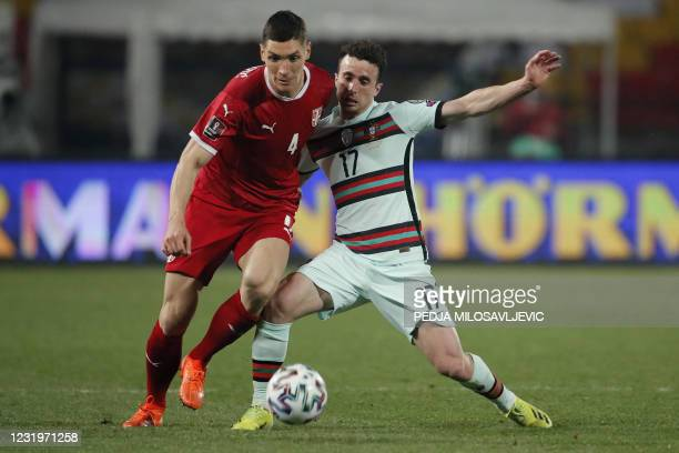 Serbia's defender Nikola Milenkovic fights for the ball with Portugal's forward Diogo Jota during the FIFA World Cup Qatar 2022 qualification Group A...