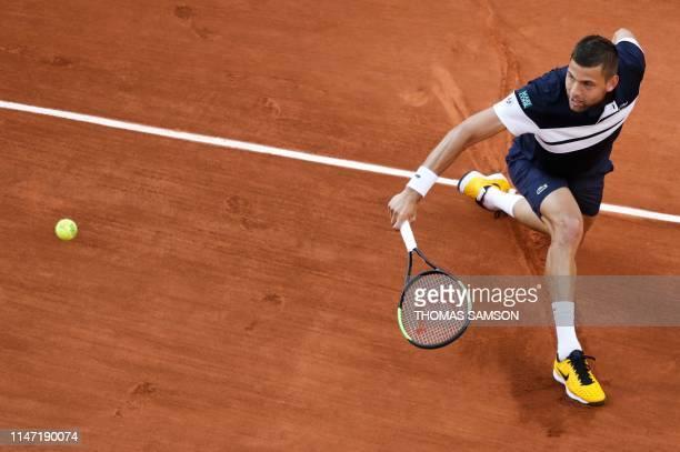 Serbia's Filip Krajinovic returns the ball to Greece's Stefanos Tsitsipas during their men's singles third round match on day six of The Roland...