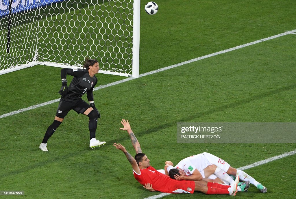 Serbia's forward Aleksandar Mitrovic (2R) after a tackle by Serbia's midfielder Adem Ljajic (R) and Switzerland's defender Stephan Lichtsteiner (hidden) during the Russia 2018 World Cup Group E football match between Serbia and Switzerland at the Kaliningrad Stadium in Kaliningrad on June 22, 2018. (Photo by Patrick HERTZOG / AFP) / RESTRICTED