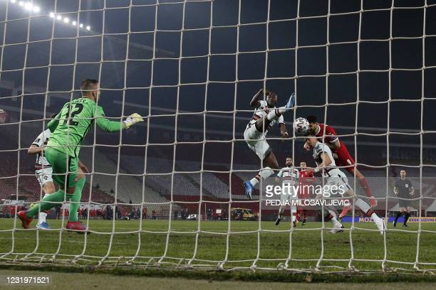 Serbia's forward Aleksandar Mitrovic heads the ball to score a goal during the FIFA World Cup Qatar 2022 qualification Group A football match between...