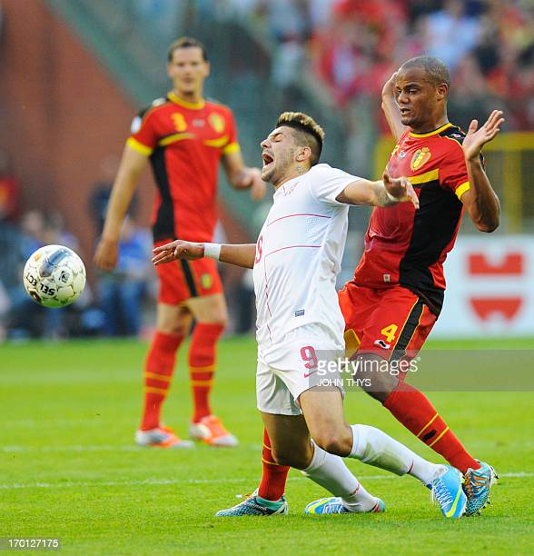 Serbia's forward Aleksandar Mitrovic vies for the ball with Belgium's defender Vincent Kompany during the 2014 World Cup Qualifying football match...