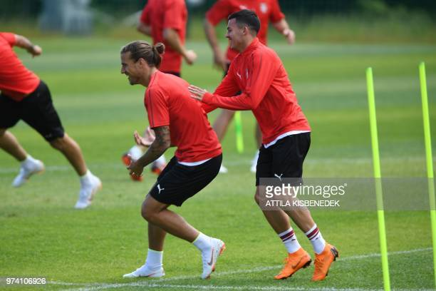 Serbia's forward Aleksandar Prijovic plays tag with his teammateNemanja Radonjic during their training session at their base camp in Svetlogorsk some...