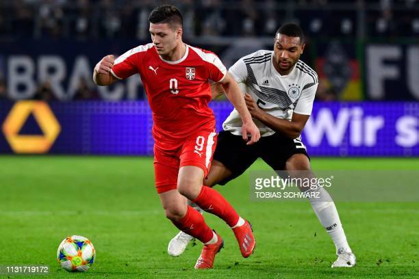 Serbia's forward Luka Jovic and Germany's defender Jonathan Tah vie for the ball during the friendly football match Germany v Serbia in Wolfsburg,...