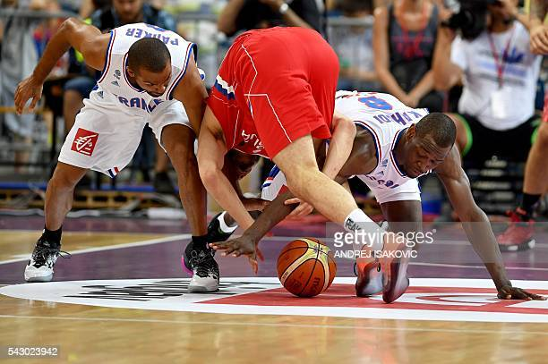 Serbia's forward Nikola Kalinic vies with France's guard Tony Parker and France's forward Charles Kahudi during the friendly basketball match between...