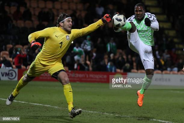 TOPSHOT Serbia's goalkeeper Vladimir Stojkovic punches the ball away from the feet of Nigeria's striker Odion Ighalo during the International...