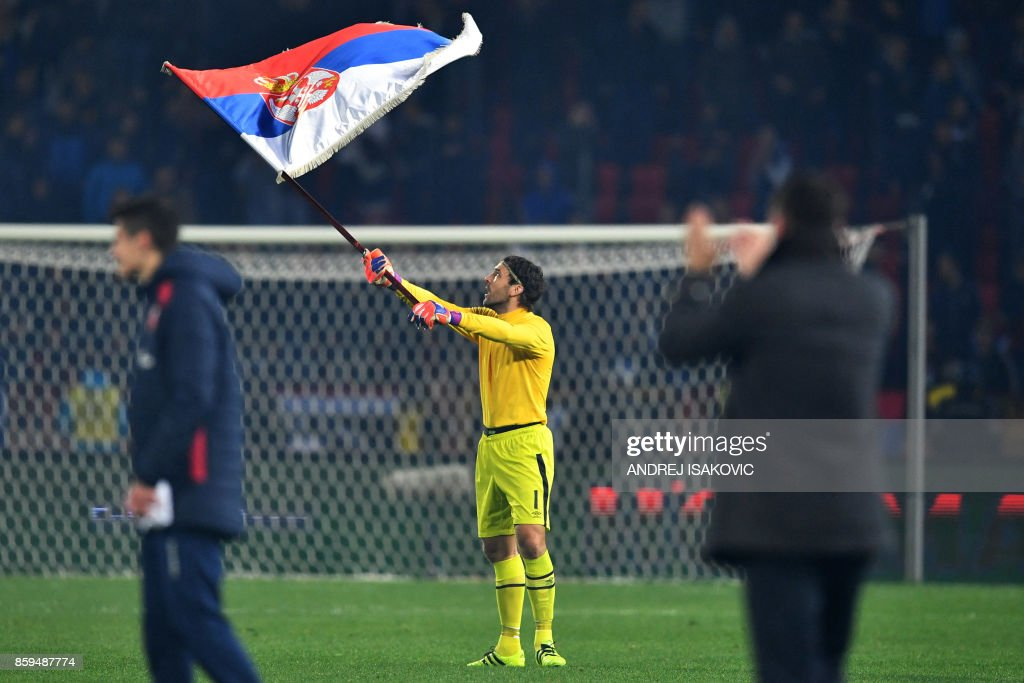 TOPSHOT - Serbia's goalkeeper Vladimir Stojkovic waves a Serbian flag as he celebrates winning the FIFA World Cup 2018 qualification football match between Serbia and Georgia at the Rajko Mitic stadium in Belgrade on October 9, 2017. /