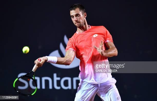 Serbia's Laslo Djere returns a ball to Austria's Dominic Thiem during their ATP World Tour Rio Open singles match at the Jockey Club in Rio de...