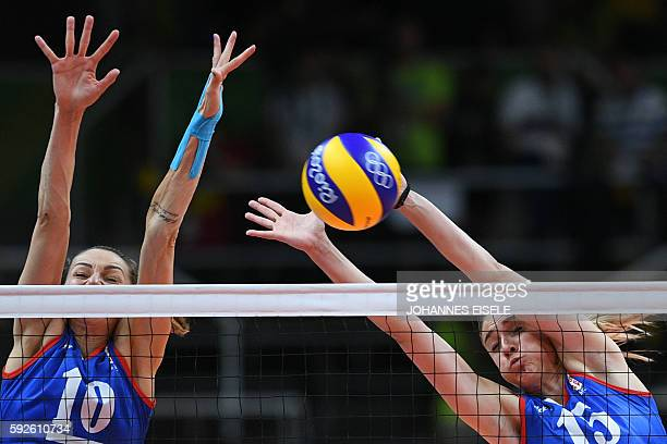 Serbia's Maja Ognjenovic and Serbia's Jovana Stevanovic jump up to block the ball during the women's Gold Medal volleyball match between China and...