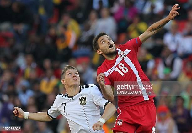 Serbia's midfielder Milos Ninkovic and Germany's midfielder Bastian Schweinsteiger jump for the ball during the Group D first round 2010 World Cup...