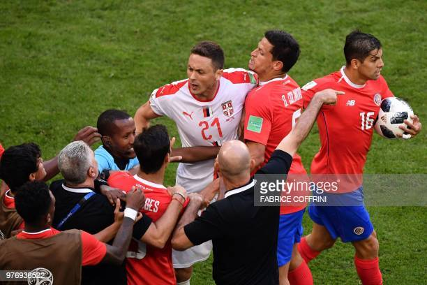 TOPSHOT Serbia's midfielder Nemanja Matic is held back by Costa Rica players following an altercation with one of their coaches during the Russia...
