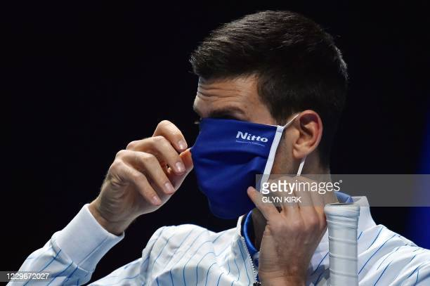 Serbia's Novak Djokovic adjusts his face mask as he arrives on court ahead of the match against Russia's Daniil Medvedev during their men's singles...