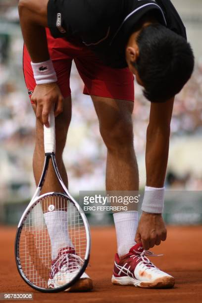 Serbia's Novak Djokovic adjusts his shoe between points against Italy's Marco Cecchinato during their men's singles quarterfinal match on day ten of...
