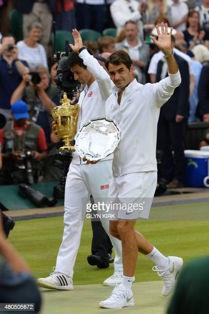 Serbia's Novak Djokovic and Switzerland's Roger Federer carry their trophies as they leave the court following thier men's singles final match...
