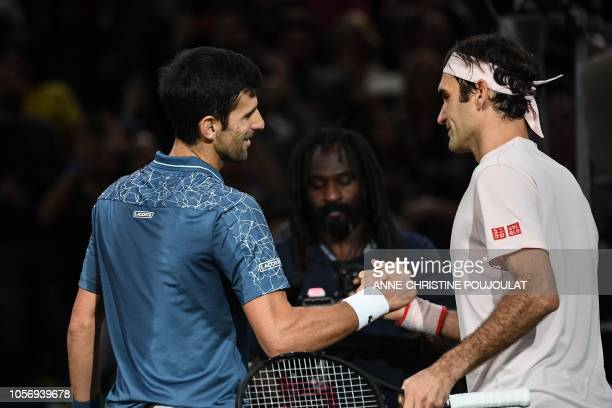TOPSHOT Serbia's Novak Djokovic and Switzerland's Roger Federer shake hands at the end of their men's singles semifinal tennis match on day six of...