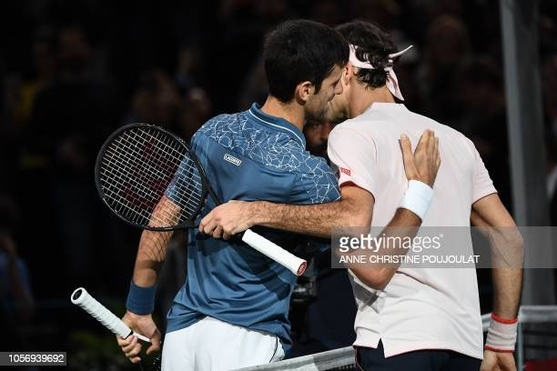 Serbia's Novak Djokovic and Switzerland's Roger Federer shake hands at the end of their men's singles semi-final tennis match on day six of the ATP...