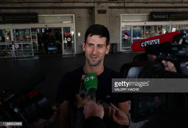 Serbia's Novak Djokovic answers journalists' questions as he arrives at Nice's airport southern France on February 4 two days after winning the men's...