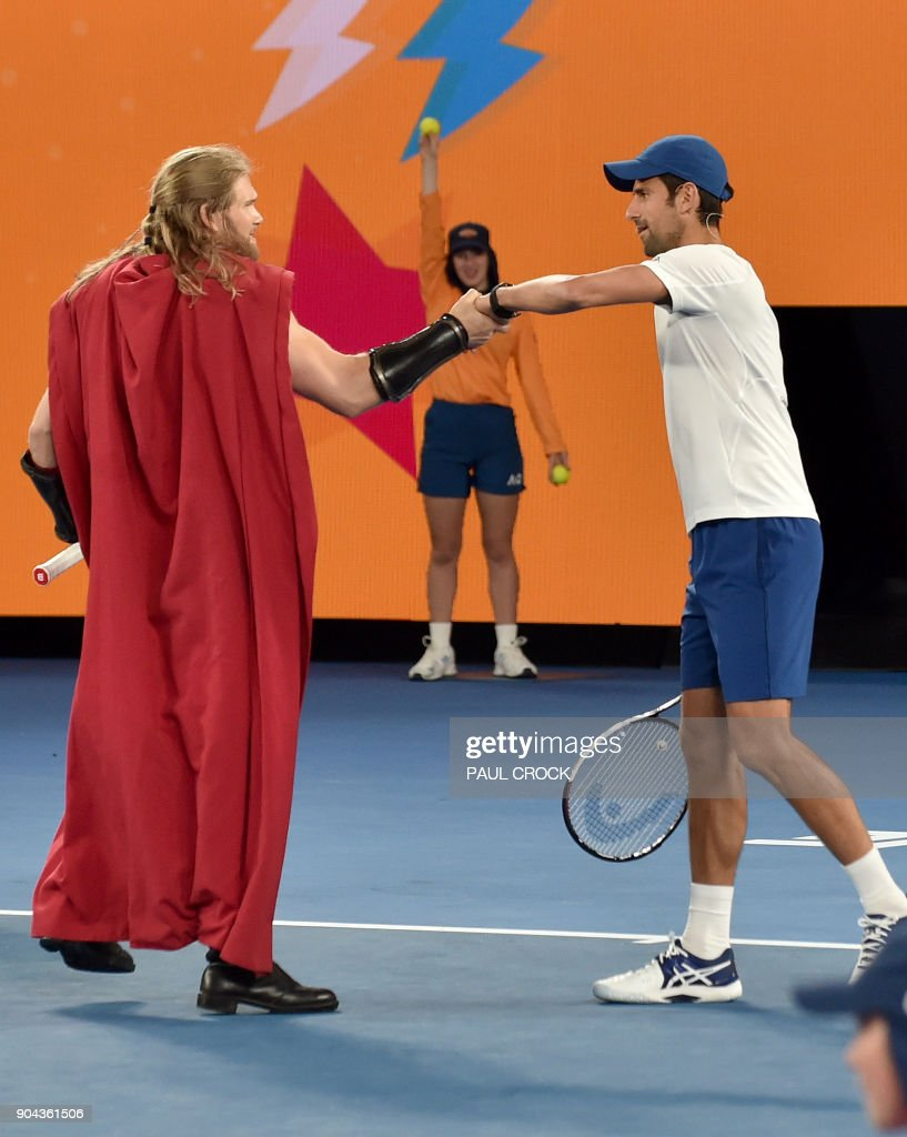 Serbia's Novak Djokovic bumps fists with an actor dressed as Marvel superhero character Thor during a Kids Day event ahead of the Australian Open tennis tournament in Melbourne on January 13, 2018. /