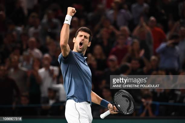 TOPSHOT Serbia's Novak Djokovic celebrates after winning against Switzerland's Roger Federer at the end of their men's singles semifinal tennis match...