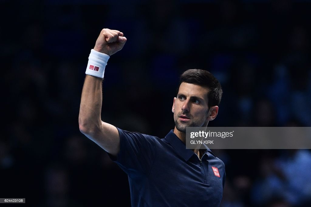 TOPSHOT - Serbia's Novak Djokovic celebrates beating Japan's Kei Nishikori during their men's semi-final singles match on day seven of the ATP World Tour Finals tennis tournament in London on November 19, 2016. / AFP PHOTO / Glyn KIRK