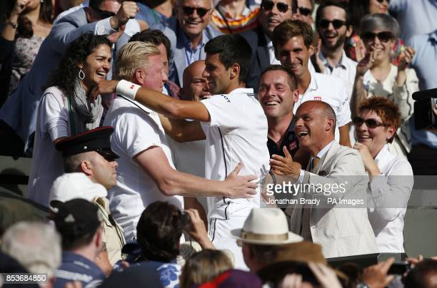 Serbia's Novak Djokovic celebrates defeating Switzerland's Roger Federer with his coach Boris Becker in the players box, following the Mens' Singles...