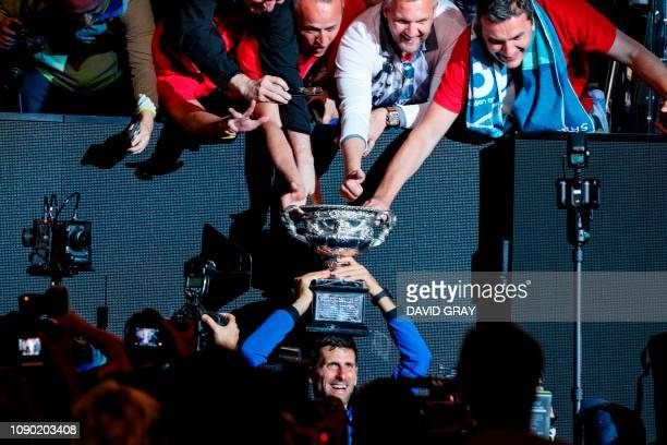 Serbia's Novak Djokovic celebrates with the championship trophy during the presentation ceremony after his victory against Spain's Rafael Nadal in...