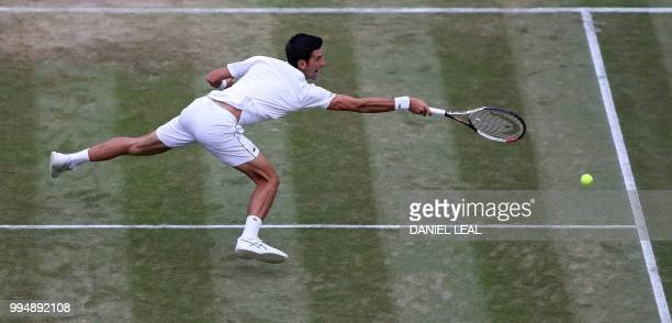 Serbia's Novak Djokovic dives to return against Russia's Karen Khachanov during their men's singles fourth round match on the seventh day of the 2018...