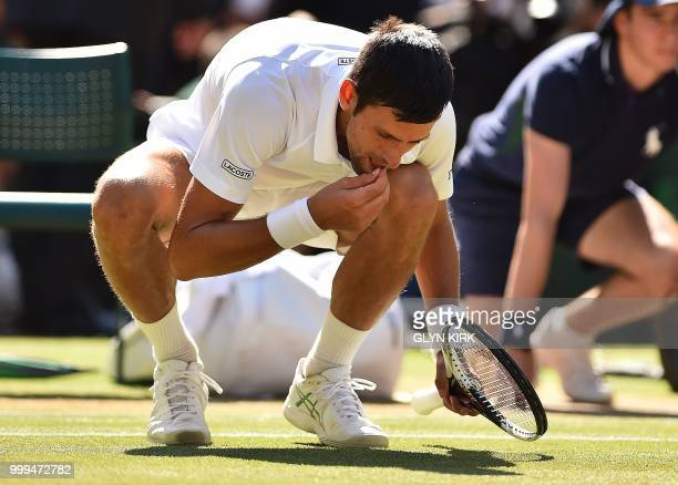Serbia's Novak Djokovic eats some grass from the court as he celebrates after beating South Africa's Kevin Anderson 62 62 76 in their men's singles...