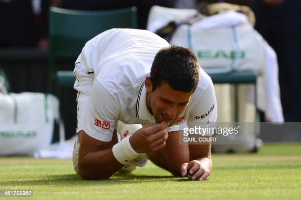 Serbia's Novak Djokovic eats the grass as he celebrates winning his men's singles final match against Switzerland's Roger Federer on day thirteen of...
